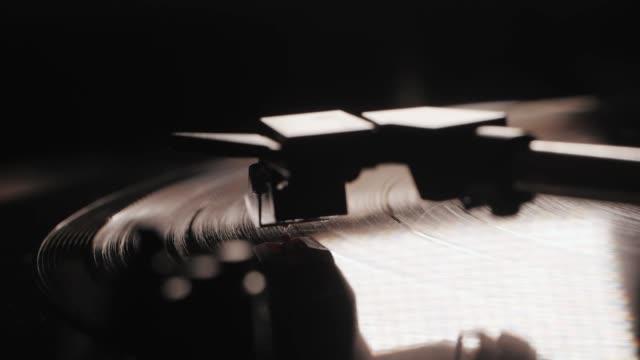 lp ターン テーブル ビニール回転を読んでのフォノまたはカプセルの頭。下りターン テーブル スタイラスのクローズ アップ。黒の 33 rpm レコードの先頭のレコード プレーヤーで再生 - アナログレコード点の映像素材/bロール