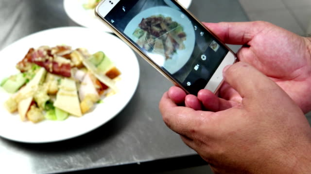 Photo Food mobile phone, the chef photographs food on professional kitchen in restaurant, Caesar salad on mobile phone screen, ready meal in the cafe video