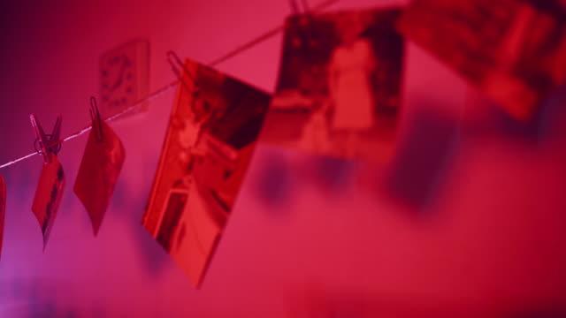 fotolaboratorium för att utveckla gamla bilder, torkade vintage svartvita bilder hängande på rep i röd fotografering mörkrum. speciell tryckutrustning i mörkrum. rad av vintage bilder i utveckla lab - sentimentalitet bildbanksvideor och videomaterial från bakom kulisserna