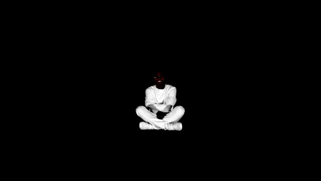 Photo of an insane black man in his forties wearing a straitjacket sitting in a dark of an asylum video