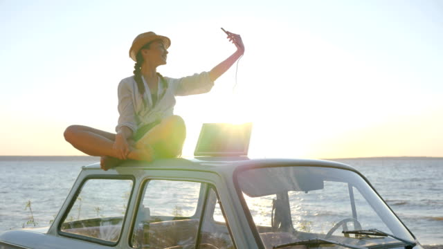 photo on automobile in sunlight, girl sits on roof retro car in backlight makes selfie on phone video