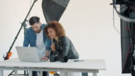 istock Photographer and model watching photos on laptop computer talking in studio 1211979227