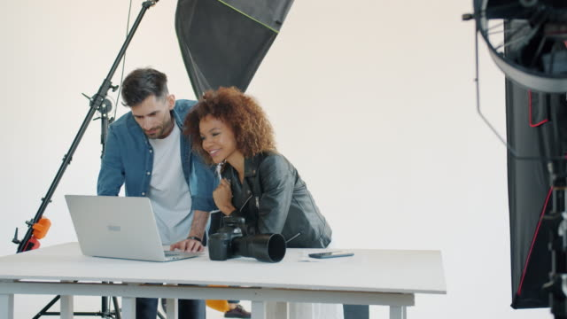 Photographer and model watching photos on laptop computer talking in studio