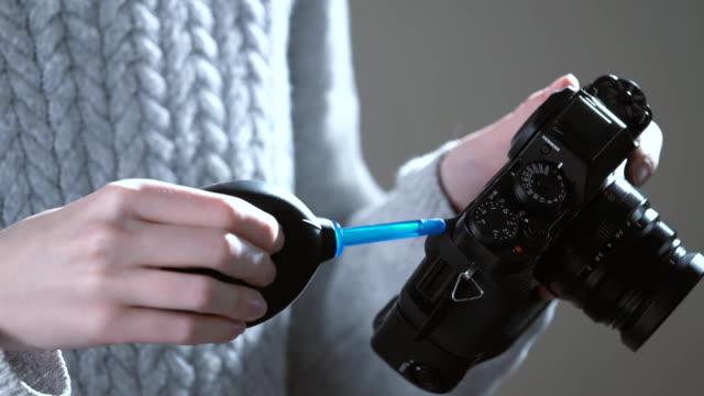 stockvideo's en b-roll-footage met fotograaf reinigen van de lens van de camera met een blower - foreground background perspective graphic