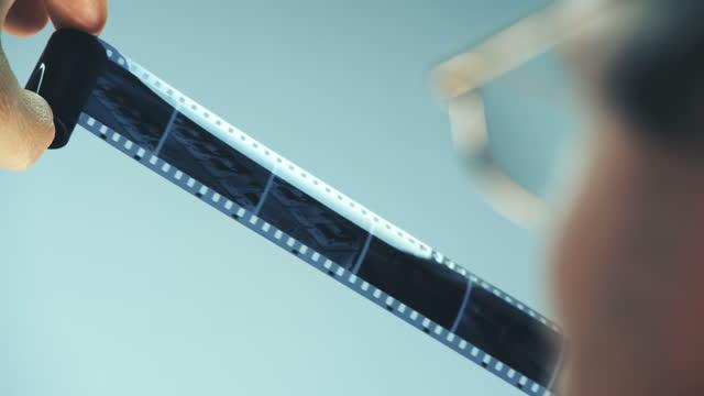 en fotograf undersöker en gammal svartvit negativ kamera rulle - diabild bildbanksvideor och videomaterial från bakom kulisserna