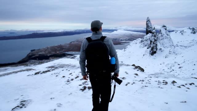 Photographer explores rugged snowy highland mountain range Scottish Highlands scotland stock videos & royalty-free footage