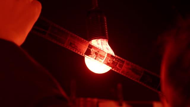 vídeos de stock e filmes b-roll de fotógrafo inspects negativos contra a luz vermelha em darkroom - fotografia imagem