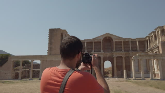 Photographer is taking photo of the Greek gymnasium of Sardis with cell phone in Sardis Ancient City