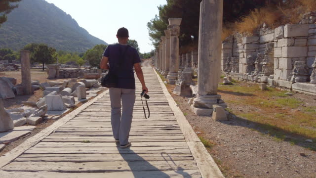 photographer is walking in ephesus ancient city - greek architecture stock videos & royalty-free footage