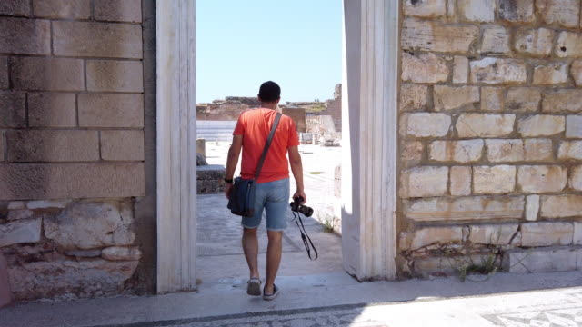 Photographer is walking to the Greek gymnasium of Sardis with cell phone in Sardis Ancient City