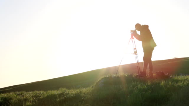 Photographer opens tripod mechanism and sets up camera at top of the green hill. video