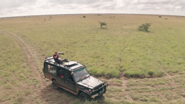 Photographer photographing from roof of vehicle while on african wildlife safari in Kenya. Aerial drone view