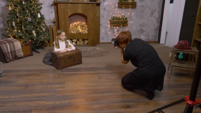 Photographer photographing girl teen on Christmas tree and fireplace background Photographer photographing girl teenager on Christmas tree and fireplace background. Backstage girl model posing in New Year photo session at decorative studio photo shoot stock videos & royalty-free footage