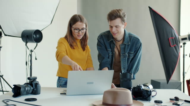 Photographer showing young man photos on laptop computer talking in studio video
