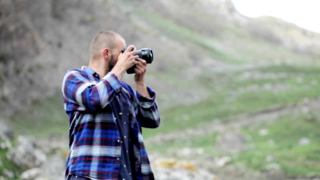 Photographer takes pictures of wildlife in the mouintains. Photographer takes pictures of wildlife in the mouintains. Traveler dressed as lumberjack style, walking and taking photo at beautiful rocky place. human joint stock videos & royalty-free footage