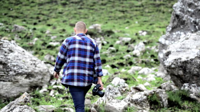 photographer takes pictures of wildlife in the mouintains. - viaggiare zaino in spalla video stock e b–roll