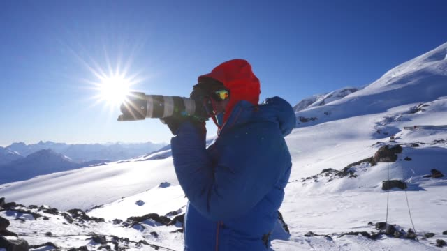 A photographer taking a picture in the cold mountains