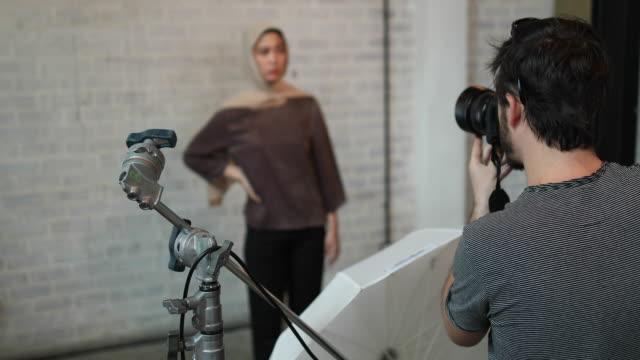 vídeos de stock, filmes e b-roll de fotógrafo para tirar uma foto de uma mulher da malásia usar hijab - temas fotográficos