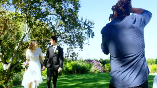 Photographer taking photo of bride and groom walking holding hands 4K 4k video