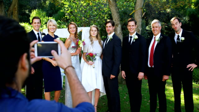 Photographer taking photo of bride and groom with there family 4K 4k video