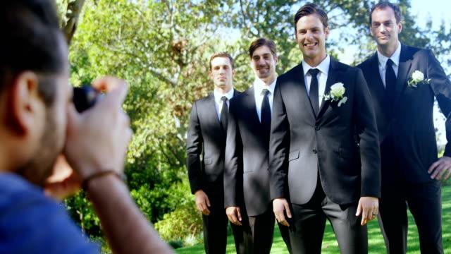 Photographer taking photo of groom and groomsmen 4K 4k video