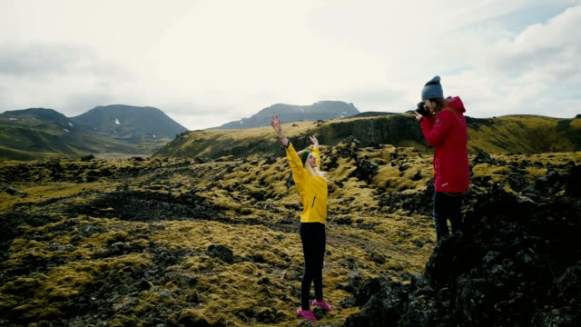 Photographer taking photo of the tourist woman in the mountains. Girls having photoshoot in lava field in Iceland
