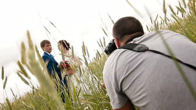 vídeos de stock, filmes e b-roll de fotógrafo tirando fotos de casal de noivos - temas fotográficos
