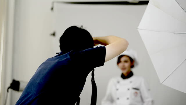 Photographer taking pictures of woman chef in the studio video