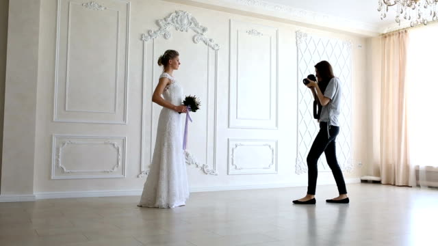Photographer taking pictures the young sexy bride Photographer with long hair is taking pictures the young sexy bride in the studio photo shoot stock videos & royalty-free footage