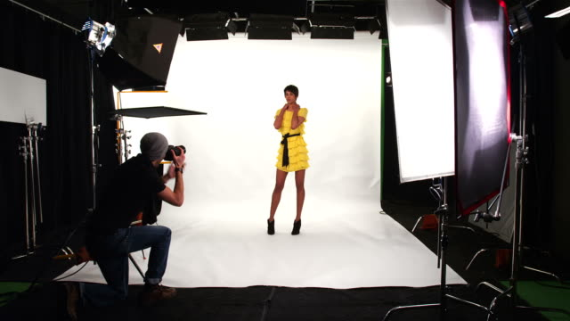 Photographer taking pictures -Uberstock- HD 1080p-  A photographer takes pictures of a fashion model in a studio.  Wide shot. photo shoot stock videos & royalty-free footage