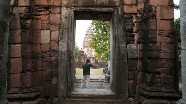vídeos de stock, filmes e b-roll de fotógrafo que toma picutres no parque histórico de phimai cénico, assentamento antigo do khmer, templo, ruínas velhas e destino do curso em tailândia do leste norte. vista traseira. - phimai