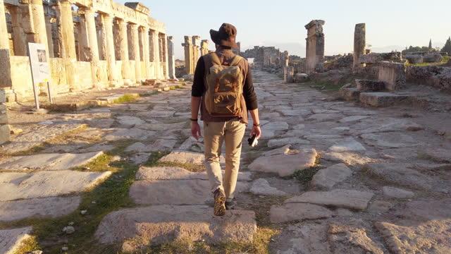 stockvideo's en b-roll-footage met fotograaf toerist loopt naar de frontinus gate in oude ruïnes in hierapolis , pamukkale - antiek toestand
