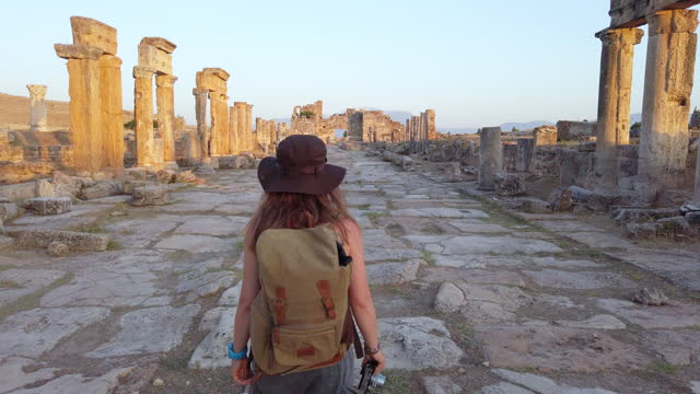 Photographer tourist is walking to the Frontinus Gate in ancient ruins in Hierapolis , Pamukkale