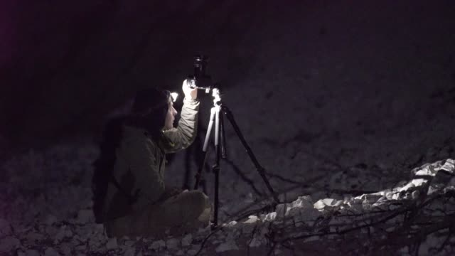 Photographer uses headlamp at night to adjust camera settings video