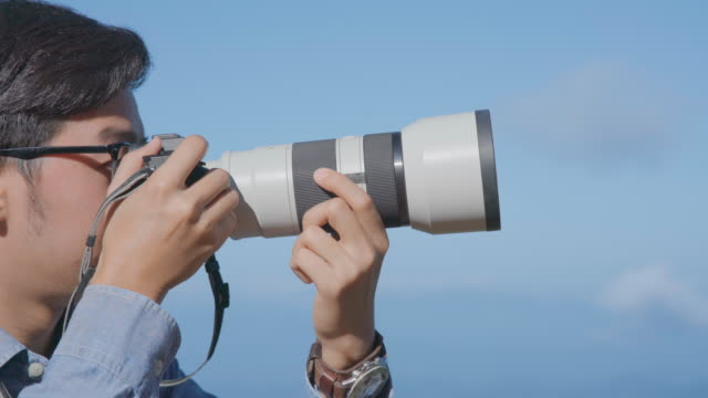 Photographer using mirrorless camera with Telephoto lens to taking a picture video