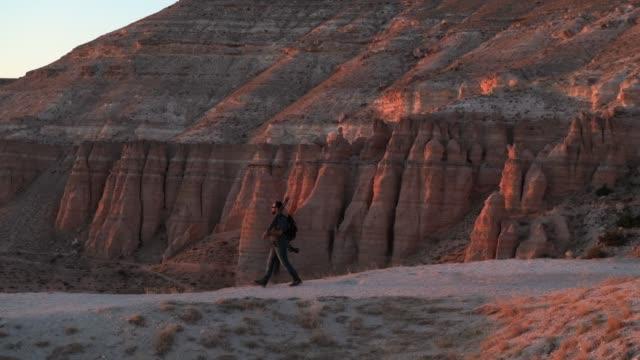 Photographer walking at sunset
