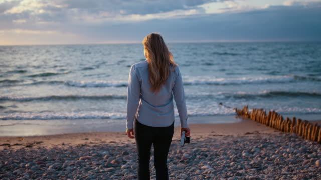 Photographer Walking Down Rocky Beach