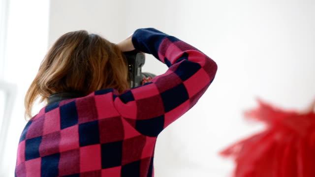 vidéos et rushes de photographe travailler avec modèle en studio. dans les coulisses - prise avec un appareil mobile