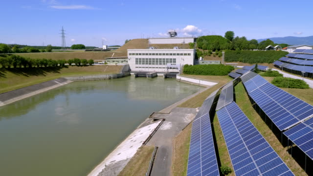 aerial photovoltaic system array on the bank of the drava river channel by the zlatolicje hydropower plant - речной канал стоковые видео и кадры b-roll