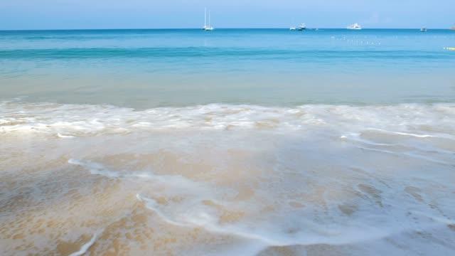 vidéos et rushes de texte de phuket sur le sable et les vagues douces s'écrasant sur la plage de phuket avec des vagues mousseuses venant à la rive, l'eau bleue de mer - mer d'andaman
