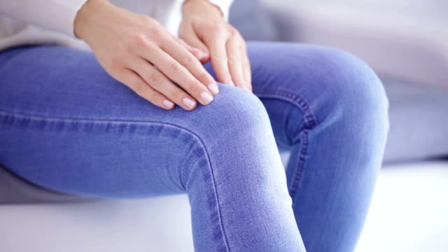 vídeos de stock, filmes e b-roll de lesões físicas de perna / joelho / conjunta - mulher segurando o corpo parte dolorosa. - articulação humana