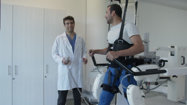 Physical therapist adjusting the speed on treadmill while patient on exoskeleton robot is learning how to walk again video