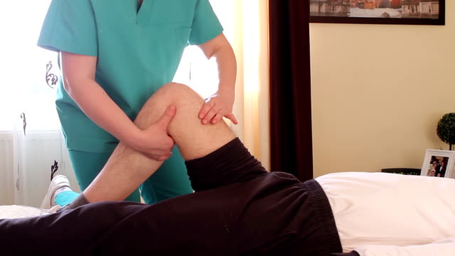 physical therapist giving a knee massage - sports medicine stock videos and b-roll footage