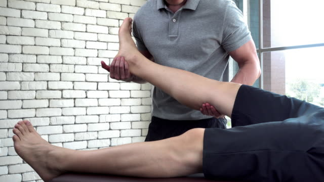physical therapist giving treatment to the broken leg patient - fisioterapia video stock e b–roll