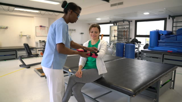 Physical therapist helping female patient wear a hand brace while both talking after physical therapy Physical therapist helping female patient wear a hand brace while both talking after physical therapy - Healthcare concepts orthopedic equipment stock videos & royalty-free footage