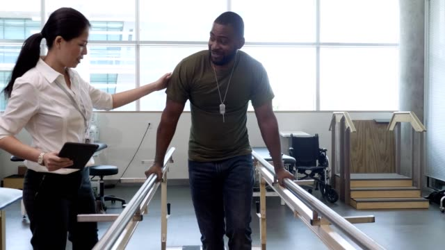 Physical therapist helps military patient on parallel bars Caring female physical therapist encourages a male soldier as he uses parallel bars to help him walk after a combat injury. veteran stock videos & royalty-free footage