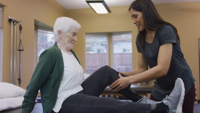 vídeos y material grabado en eventos de stock de fisioterapeuta, masaje músculo de la pantorrilla de tercera edad mujer - geriatría