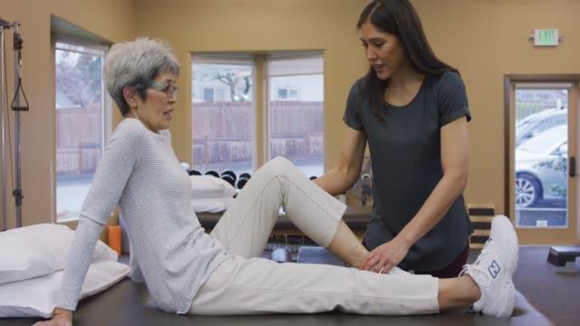 physical therapist massaging senior female's calf muscle - fisioterapia video stock e b–roll