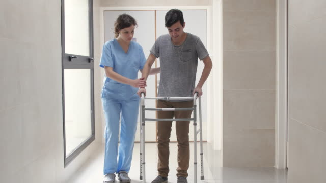 physical therapist motivating her patient while he was with effort using a walker through the hospital's hallway - wyzwanie filmów i materiałów b-roll