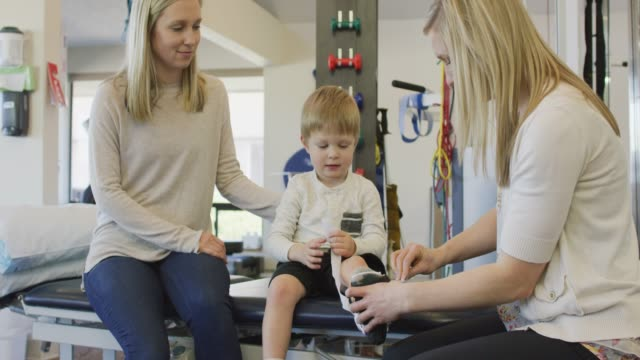physical therapist placing soft cast on child - fisioterapia video stock e b–roll